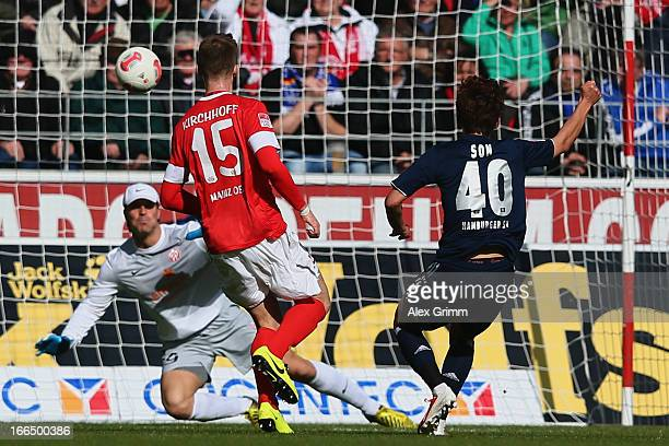 HeungMin Son of Hamburg scores his team's first goal against Jan Kirchhoff and goalkeeper Christian Wetklo of Mainz during the Bundesliga match...