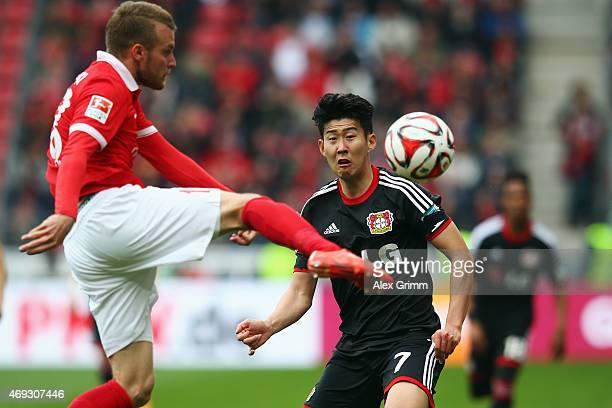 HeungMin Son of Leverkusen is challenged by Daniel Brosinski of Mainz during the Bundesliga match between 1 FSV Mainz 05 and Bayer 04 Leverkusen at...