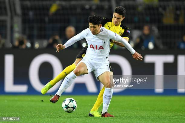 HeungMin Son of Tottenham Hotspur and Marc Bartra of Borussia Dortmund battle for possession during the UEFA Champions League group H match between...