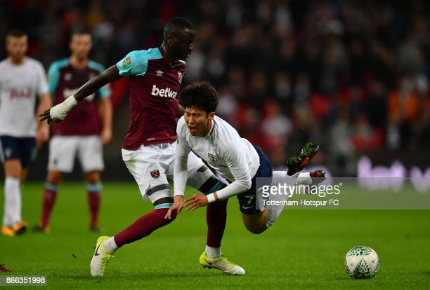 HeungMin Son of Tottenham Hotspur is tackled by Cheikhou Kouyate of West Ham United during the Carabao Cup Fourth Round match between Tottenham...