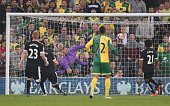 Heurelho Gomes of Watford is unable to stop an own goal by Craig Cathcart of Watford during the Barclays Premier League match between Norwich City...