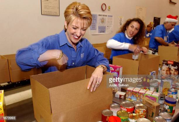 Hewlett Packard CEO Carly Fiorina laughs with HP employee Priscilla Friedlander as they pack boxes while volunteering at the Second Harvest Food Bank...
