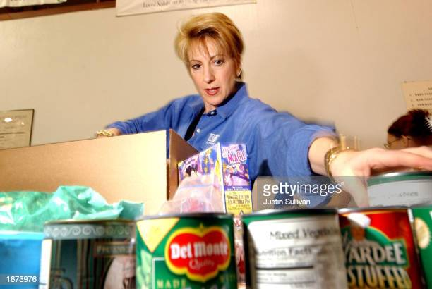 Hewlett Packard CEO Carly Fiorina packs boxes as she volunteers with other HP employees at the Second Harvest Food Bank December 5 2002 in San Jose...