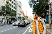Handsome hipster with orange jacket and sunglasses stopping taxi in the city street