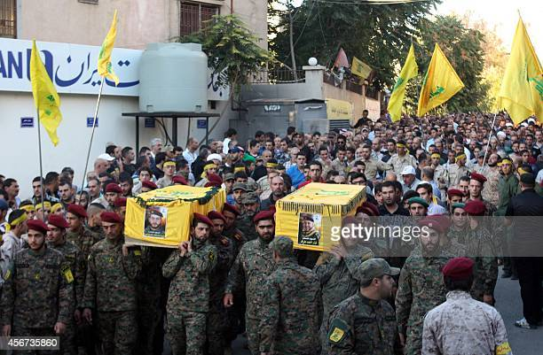 Hezbollah fighters carry the coffin of fellow Shiite militant Nizar Tarraf and Mohammad Murtada during their funeral in the town of Baalbek in...