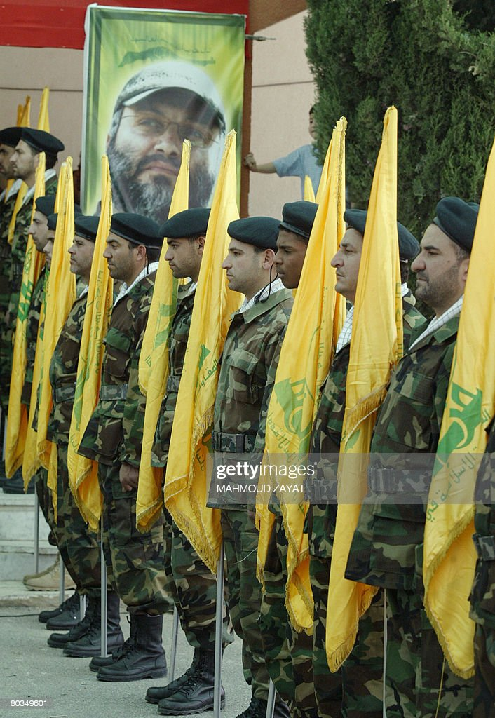 Hezbollah fighters parade with the Shiite militia's yellow flags during a memorial ceremony held for the group's slain commander Imad Mughnieh in the...