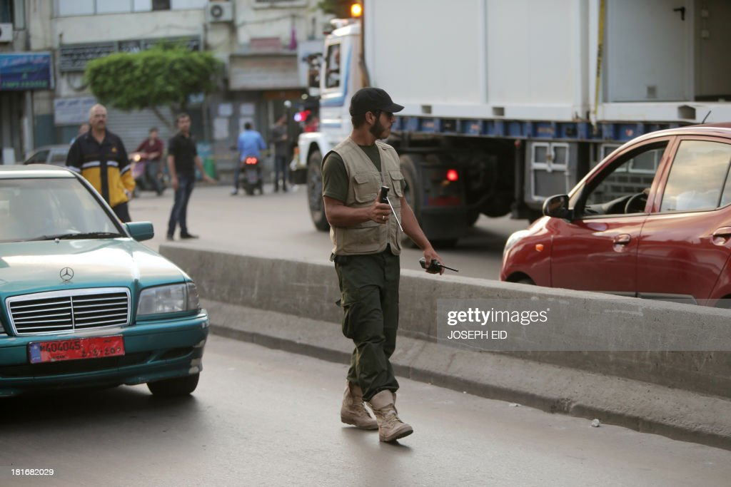 A Hezbollah militant checks cars for bombs and explosives in a street in the southern suburb of the Lebanese capital Beirut on September 23, 2013. Lebanese troops are to take over security at checkpoints set up by the Hezbollah movement in their southern Beirut stronghold after two bombings, the interior minister told AFP.