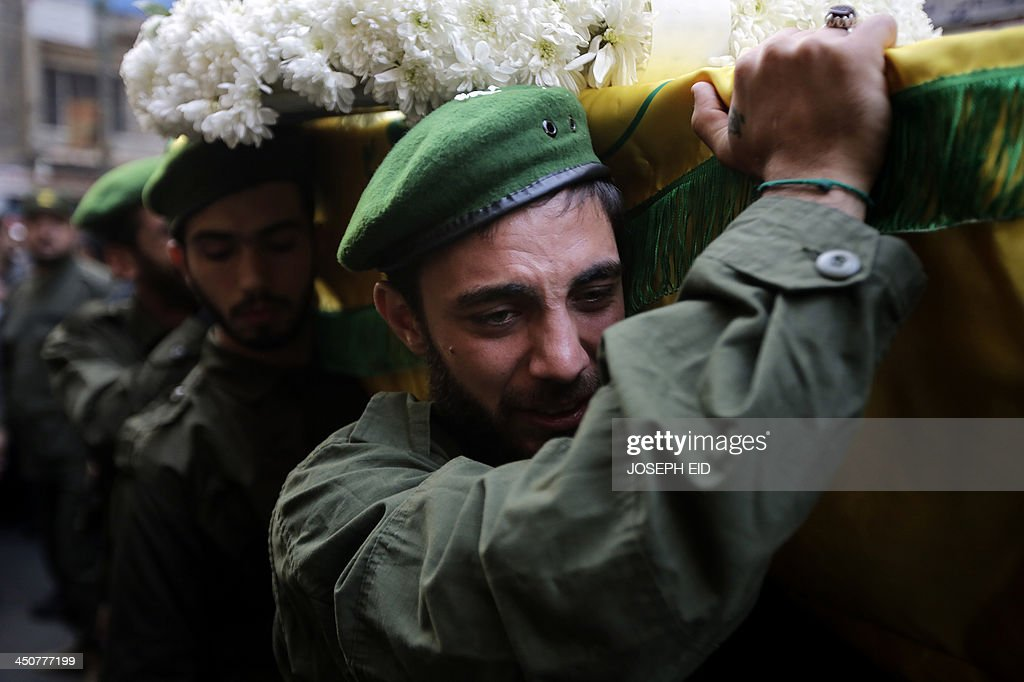 A Hezbollah militant mourns the death of one his comrades who died in the twin suicide attack outside the Iranian Embassy in Beirut the previous day, as he carries his coffin during his funeral in Shiah, a southern suburb of the Lebanese capital, on November 20, 2013. Thousands of people turned out for a funeral for the four Iranian embassy security guards, all of whom were members of Lebanon's powerful Shiite movement Hezbollah, which is also backed by Iran and is fighting alongside Assad's troops against Sunni-led rebels.