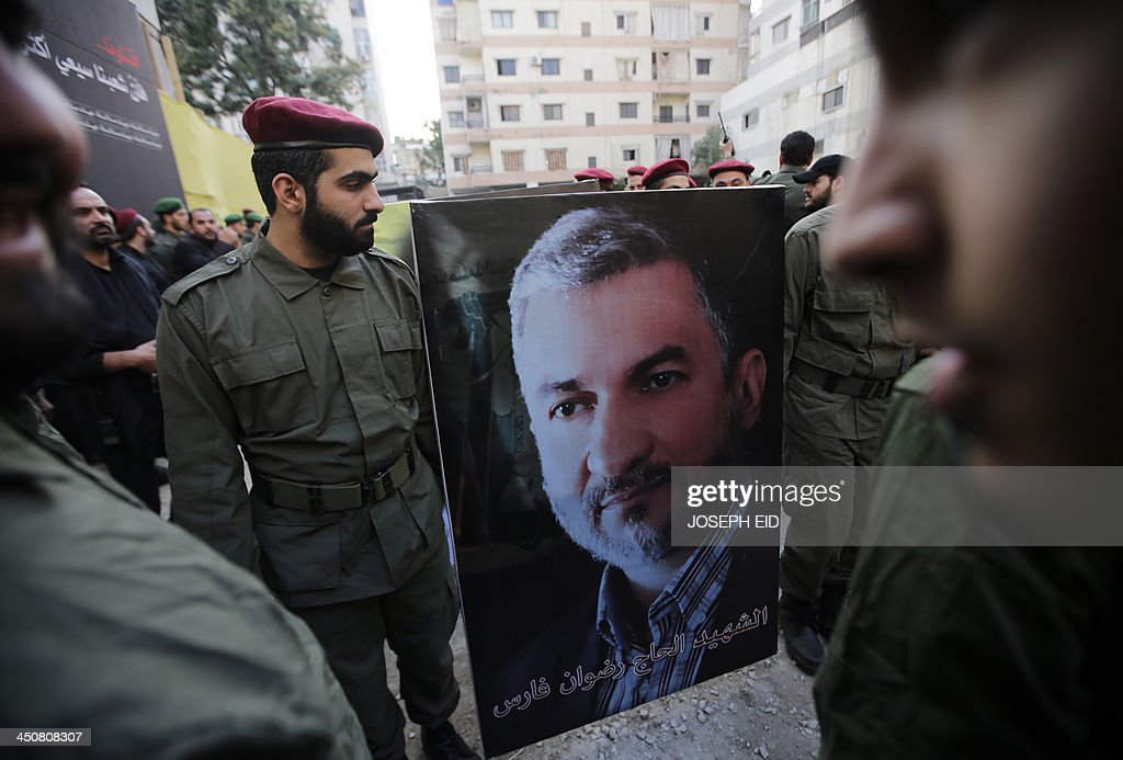 Hezbollah militants carry a poster of the head of the Iranian embassy security Radwan Fares who was killed in the suicide attack outside the Iranian Embassy in Beirut the previous day, during the funeral in Shiah, a southern suburb of the Lebanese capital, of the four Iranian embassy security guards who died in the attack on November 20, 2013. Thousands of people turned out for a funeral for the four Iranian embassy security guards, all of whom were members of Lebanon's powerful Shiite movement Hezbollah, which is also backed by Iran and is fighting alongside Assad's troops against Sunni-led rebels.
