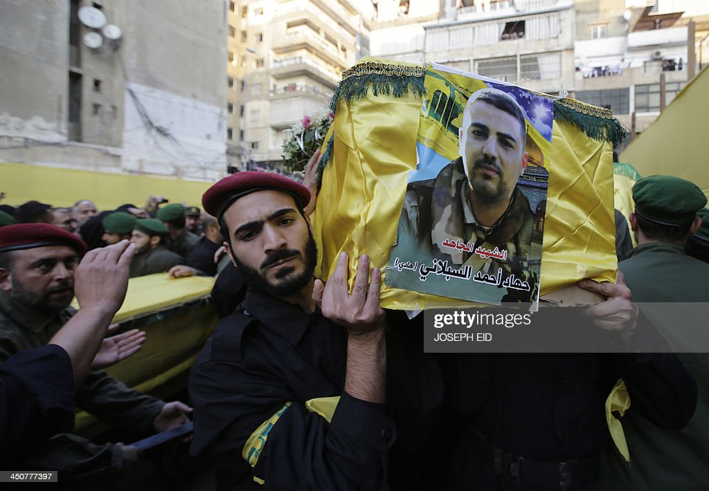 Hezbollah militants carry the coffin of one of their comrades, draped in the movement's yellow and green flag, who died in the twin suicide attack outside the Iranian Embassy in Beirut the previous day, during their funeral in Shiah, a southern suburb of the Lebanese capital on November 20, 2013. Thousands of people turned out for a funeral for the four Iranian embassy security guards, all of whom were members of Lebanon's powerful Shiite movement Hezbollah, which is also backed by Iran and is fighting alongside Assad's troops against Sunni-led rebels. AFP PHOTO/JOSEPH EID