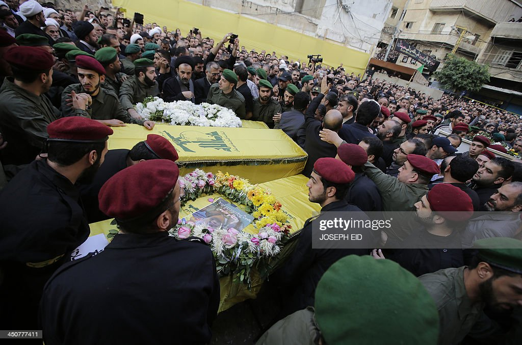 Hezbollah militants carry the coffins of their comrades, draped in the movement's yellow and green flags, who died in the twin suicide attack outside the Iranian Embassy in Beirut the previous day, during their funeral in Shiah, a southern suburb of the Lebanese capital on November 20, 2013. Thousands of people turned out for a funeral for the four Iranian embassy security guards, all of whom were members of Lebanon's powerful Shiite movement Hezbollah, which is also backed by Iran and is fighting alongside Assad's troops against Sunni-led rebels.