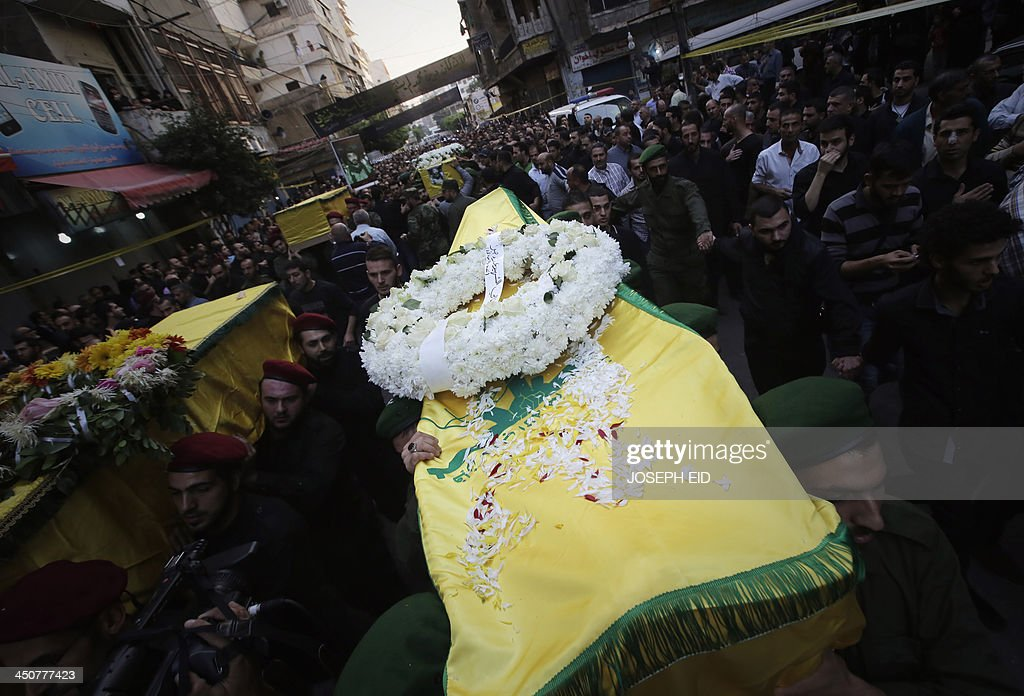 Hezbollah militants carry the coffins of their comrades, draped in the movement's yellow and green flags, who died in the twin suicide attack outside the Iranian Embassy in Beirut the previous day, during their funeral in Shiah, a southern suburb of the Lebanese capital on November 20, 2013. Thousands of people turned out for a funeral for the four Iranian embassy security guards, all of whom were members of Lebanon's powerful Shiite movement Hezbollah, which is also backed by Iran and is fighting alongside Assad's troops against Sunni-led rebels. AFP PHOTO/JOSEPH EID