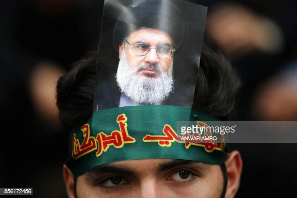 A Hezbollah supporter displays a picture of Lebanon's Hezbollah chief Hasan Nasrallah as he marks Ashura in a southern suburb of the Lebanese capital...