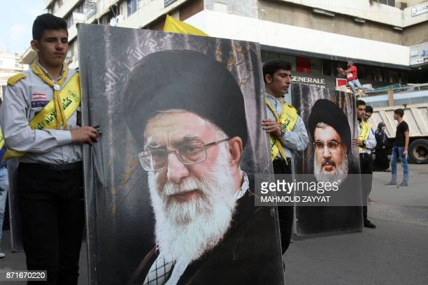 Hezbollah supporters carry posters of the head of the Lebanese Shiite movement Hezbollah Hasan Nasrallah and Iran's Supreme Leader Ayatollah Ali...