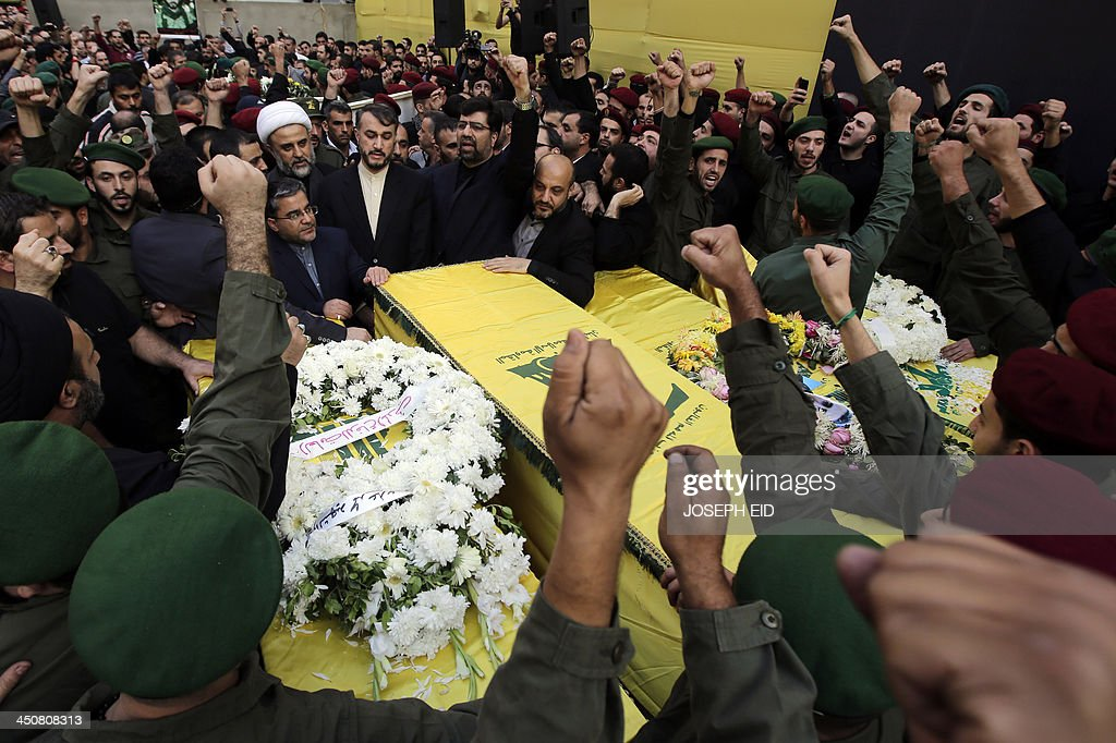 Hezbollah's military chief in south Lebanon Sheikh Nabil Qawuq (C-L), Iranian Ambassador to Lebanon Ghadanfar Rukn Abadi (C-R) and Iranian Deputy Foreign Minister Hossein Amir Abdollahian (C) stand next to the coffins of the Iranian embassy security guards, draped in the Hezbollah movement's yellow and green flag, who died in the suicide attack outside the Iranian Embassy in Beirut the previous day, during their funeral in Shiah, a southern suburb of the Lebanese capital on November 20, 2013. Thousands of people turned out for a funeral for the four Iranian embassy security guards, all of whom were members of Lebanon's powerful Shiite movement Hezbollah, which is also backed by Iran and is fighting alongside Assad's troops against Sunni-led rebels. AFP PHOTO/JOSEPH EID