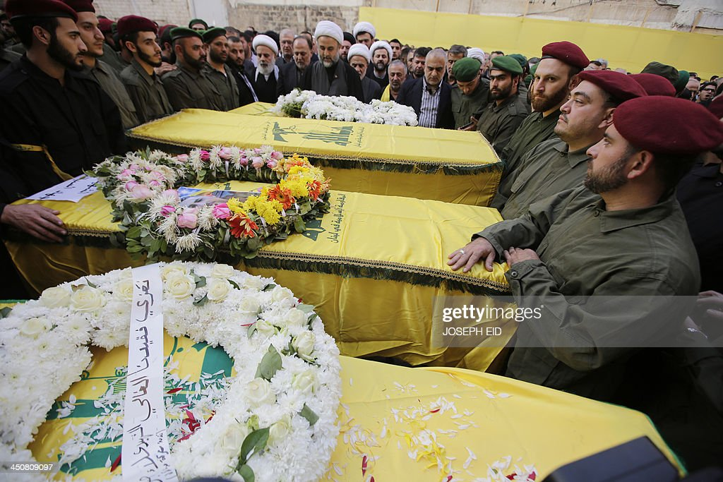 Hezbollah's military chief in south Lebanon Sheikh Nabil Qawuq (C-back) prays next to the coffins of the Iranian embassy security guards, draped in the Hezbollah movement's yellow and green flag, who died in the suicide attack outside the Iranian Embassy in Beirut the previous day, during their funeral in Shiah, a southern suburb of the Lebanese capital on November 20, 2013. Thousands of people turned out for a funeral for the four Iranian embassy security guards, all of whom were members of Lebanon's powerful Shiite movement Hezbollah, which is also backed by Iran and is fighting alongside Assad's troops against Sunni-led rebels.