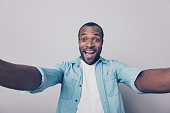 Hi guys! Portrait of adorable excited amazed funny joyful african man taking self portrait while having a trip around the world isolated on gray background