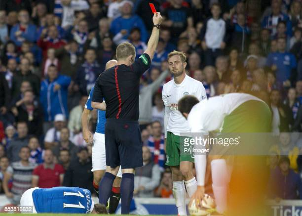 Hibernian's Danny Handling is shown a red card by referee John Beaton during the Petrofac Training Cup match at Ibrox Glasgow