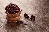 Hibiscus (Roselle, karkade) dry flowers in bowles on wooden background with copyspace. Healthy organic vitamin herbal tea.