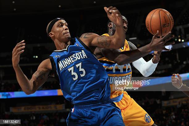 J Hickson of the Denver Nuggets grabs a rebound away from Dante Cunningham of the Minnesota Timberwolves at Pepsi Center on November 15 2013 in...
