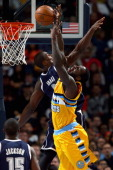 J Hickson of the Denver Nuggets lays up a shot against Serge Ibaka of the Oklahoma City Thunder and is fouled by Kendrick Perkins of the Oklahoma...