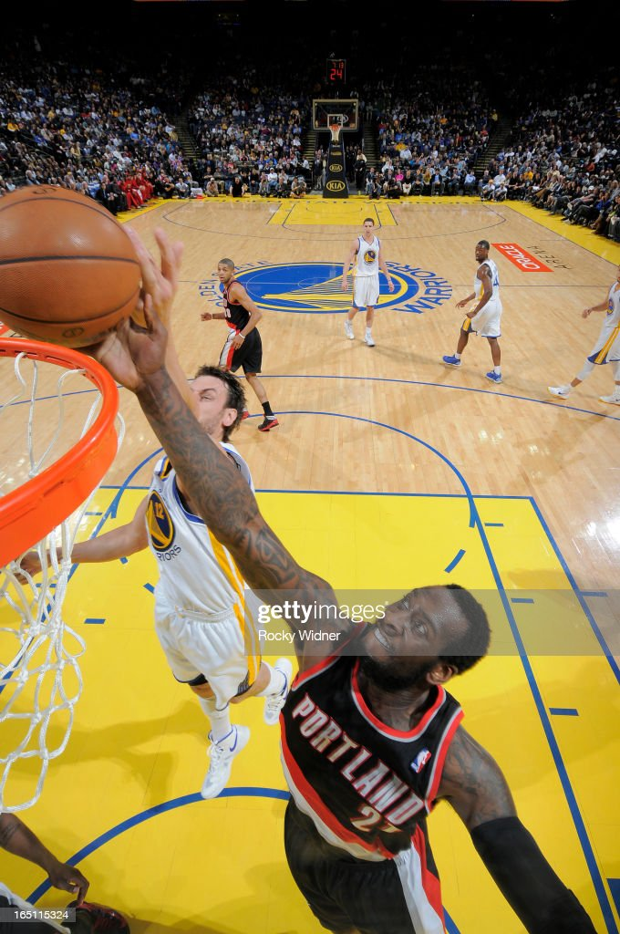 J.J. Hickson #21 of the Portland Trail Blazers rebounds against Andrew Bogut #12 of the Golden State Warriors on March 30, 2013 at Oracle Arena in Oakland, California.