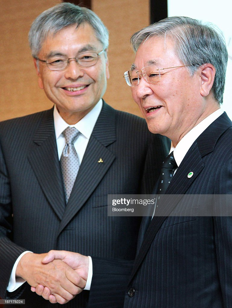 Hideaki Omiya, president and chief executive officer of Mitsubishi Heavy Industries Ltd., left, shakes hands with Hiroaki Nakanishi, president of Hitachi Ltd., during a joint news conference in Tokyo, Japan, on Thursday, Nov. 29, 2012. Mitsubishi Heavy Industries and Hitachi agreed to merge power-equipment businesses with combined sales of 1.1 trillion yen ($13 billion) to bolster their product line-ups and global sales reach. Photographer: Haruyoshi Yamaguchi/Bloomberg via Getty Images