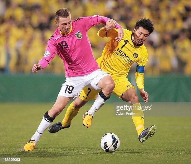 Hidekazu Otani of Kashiwa Reysol tackles Mitchell Duke of the Mariners during the AFC Champions League Group H match between Kashiwa Reysol and...