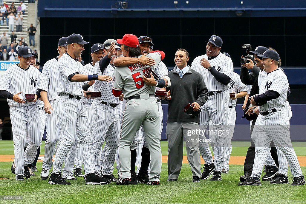 <a gi-track='captionPersonalityLinkClicked' href=/galleries/search?phrase=Hideki+Matsui&family=editorial&specificpeople=157483 ng-click='$event.stopPropagation()'>Hideki Matsui</a> #55 of the Los Angeles Angels of Anaheim is greeted by former teammates including <a gi-track='captionPersonalityLinkClicked' href=/galleries/search?phrase=Derek+Jeter&family=editorial&specificpeople=167125 ng-click='$event.stopPropagation()'>Derek Jeter</a> #2 (2nd L) and Alex Rodriguez #13 (C) of the New York Yankees after Matsui received his World Series ring for being a member of the 2009 New York Yankees Worlder Series Championship team prior to playing against the New York Yankees during the Yankees home opener at Yankee Stadium on April 13, 2010 in the Bronx borough of New York City.