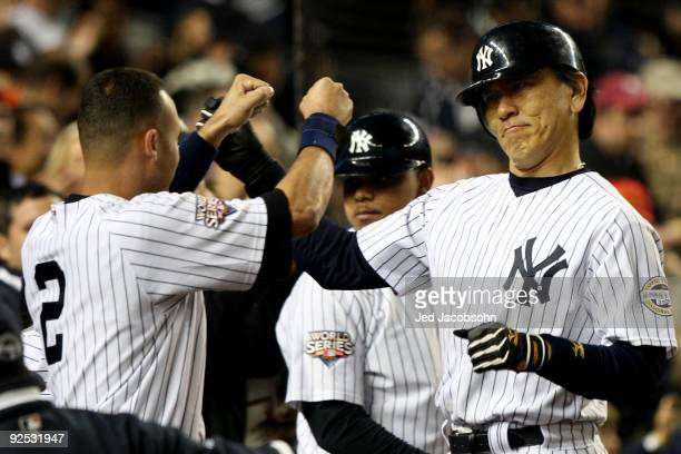 Hideki Matsui of the New York Yankees celebrates with Derek Jeter after hitting a solo home run in the sixth inning against the Philadelphia Phillies...