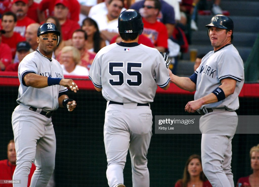 Hideki Matsui of the New York Yankees (55) is greeted by Gary Sheffield (left) and Jason Giambi after scoring in the first inning of 4-2 victory over the Los Angeles Angels of Anaheim in MLB Division Series American League playoff game at Angel Stadium in Anaheim, Calif. on Tuesday, October 4, 2005.