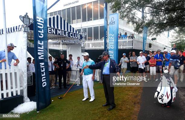 Hideki Matsuyama left listens as a rules official right explains what he must do after hitting his ball up along a suite area on the 16th fairway...