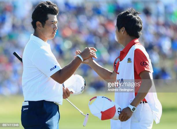 Hideki Matsuyama of Japan and caddie Daisuke Sindo react after finishing on the 18th green during the final round of the 2017 US Open at Erin Hills...