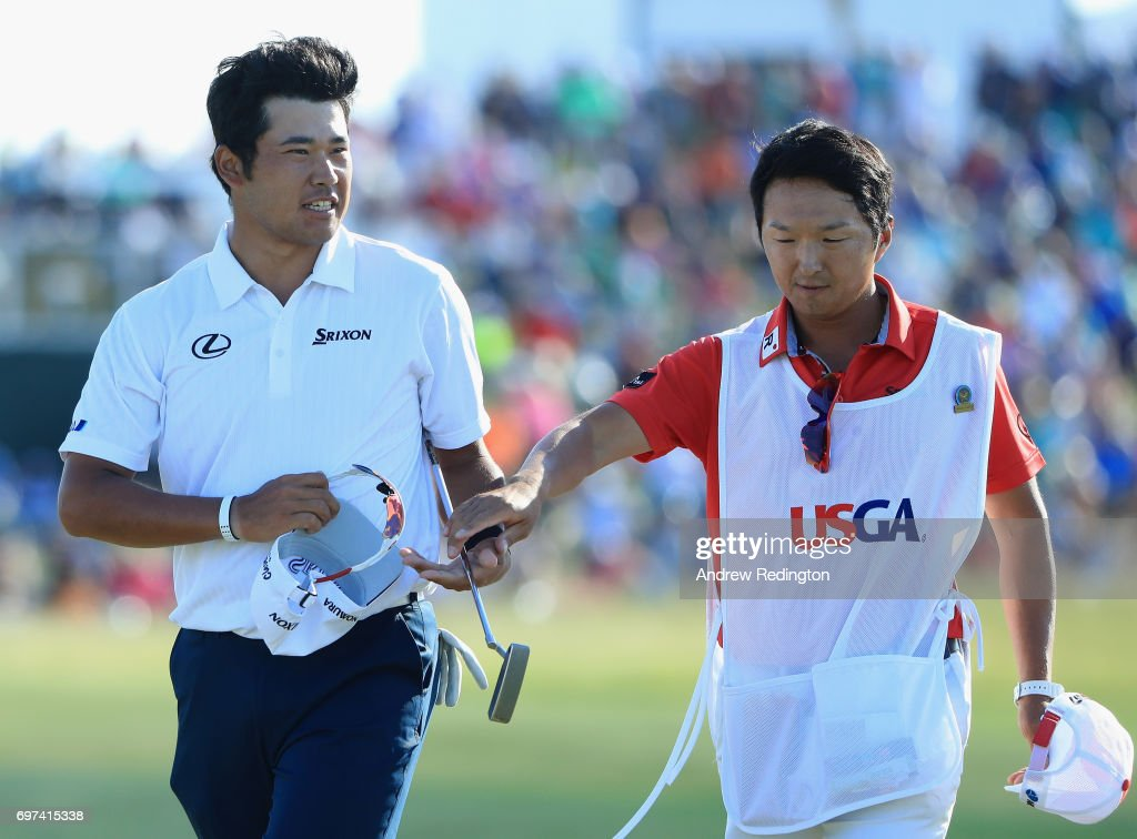 Hideki Matsuyama of Japan and caddie Daisuke Sindo react after finishing on the 18th green during the final round of the 2017 U.S. Open at Erin Hills on June 18, 2017 in Hartford, Wisconsin.