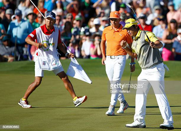Hideki Matsuyama of Japan celebrates a birdie putt on the 18th hole as Rickie Fowler looks on during the final round of the Waste Management Phoenix...