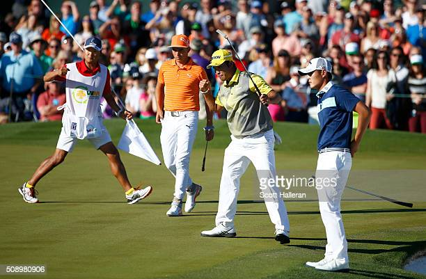 Hideki Matsuyama of Japan celebrates a birdie putt on the 18th hole as Rickie Fowler and Danny Lee of New Zealand look on during the final round of...
