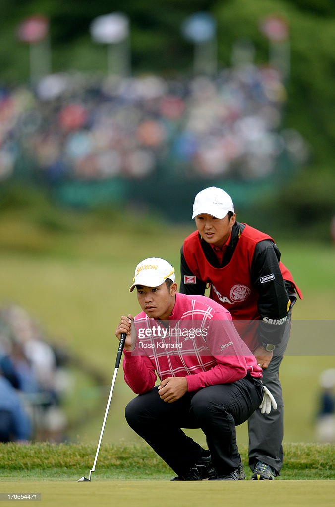 Hideki Matsuyama of Japan lines up a putt with the help of his caddie Daisuke Shindo on the 18th green during a continuation of Round One of the 113th U.S. Open at Merion Golf Club on June 14, 2013 in Ardmore, Pennsylvania.