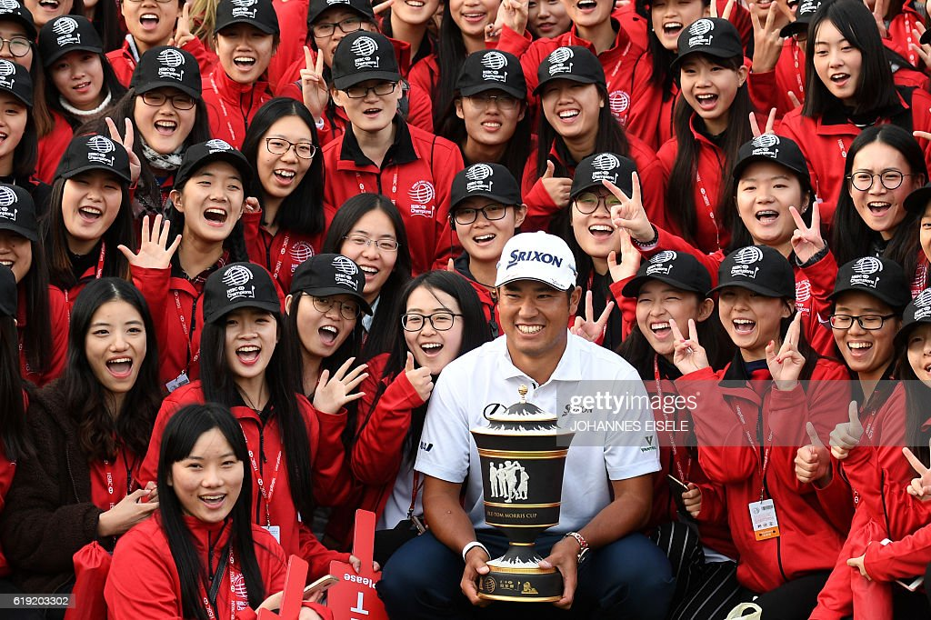 Hideki Matsuyama (C) of Japan poses with the winner's trophy after the final round of the World Golf Championships-HSBC Champions golf tournament in Shanghai on October 30, 2016. / AFP / JOHANNES