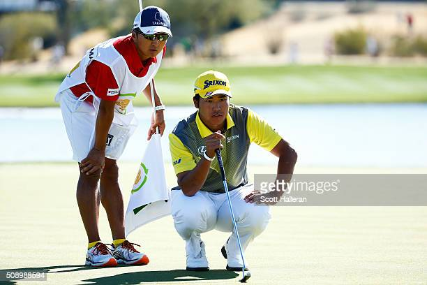 Hideki Matsuyama of Japan talks with his caddie Daisuke Shindo as he prepares to putt during the final round of the Waste Management Phoenix Open at...