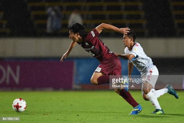 Hideto Takahashi of Vissel Kobe controls the ball under pressure of Chanathip Songkrasin of Consadole Sappporo during the JLeague J1 match between...