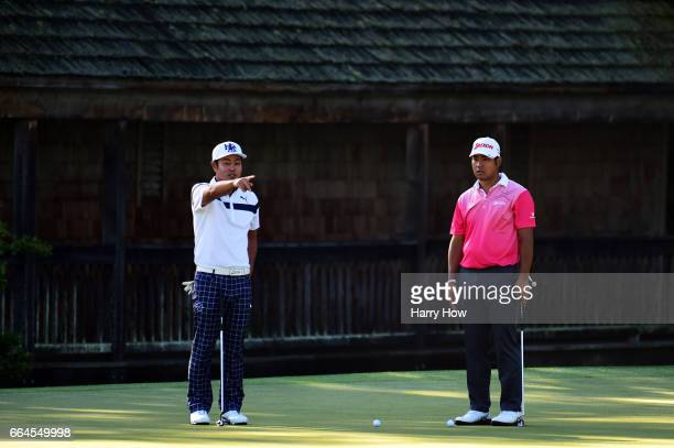 Hideto Tanihara of Japan and Hideki Matsuyama of Japan wait on the 11th green during a practice round prior to the start of the 2017 Masters...