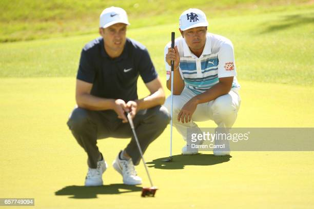 Hideto Tanihara of Japan and Ross Fisher of England line up putts on the 11th hole of their match during round five of the World Golf...