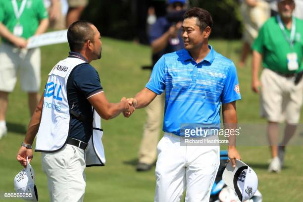Hideto Tanihara of Japan celebrates with his caddie after defeating Jordan Spieth on the 16th hole of their match during round one of the World Golf...