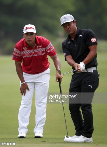 Hideto Tanihara of Japan chips onto the green as Hideki Matsuyama of Japan looks on during the third round of the Zurich Classic at TPC Louisiana on...