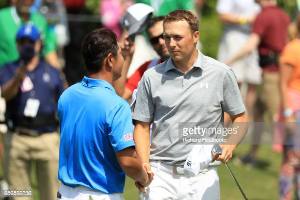 Hideto Tanihara of Japan shakes hands with Jordan Spieth after defeating him on the 16th hole of their match during round one of the World Golf...