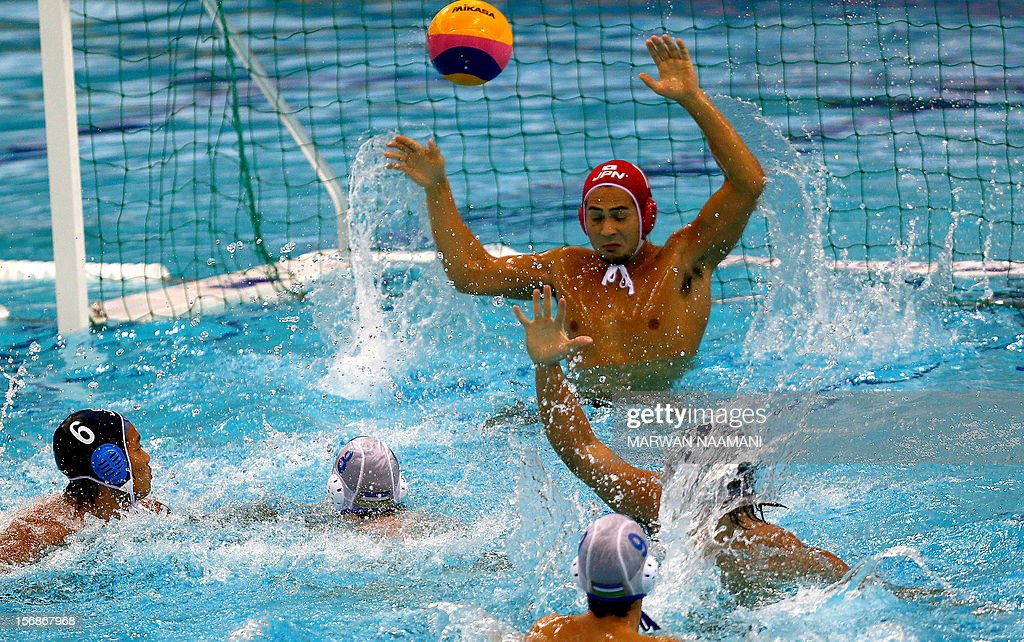 Hideyuki Tanamura (C) goalkeeper of Japan tries to save a shot by Kirill Rustamov of Uzbeksitan (unseen) during their quaterfinal water polo game at the 9th Asian Swimming Championships in Dubai, on November 23 2012.
