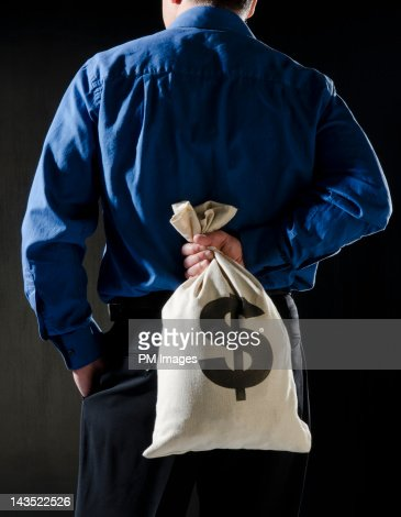 Hiding money behind the back : Foto de stock