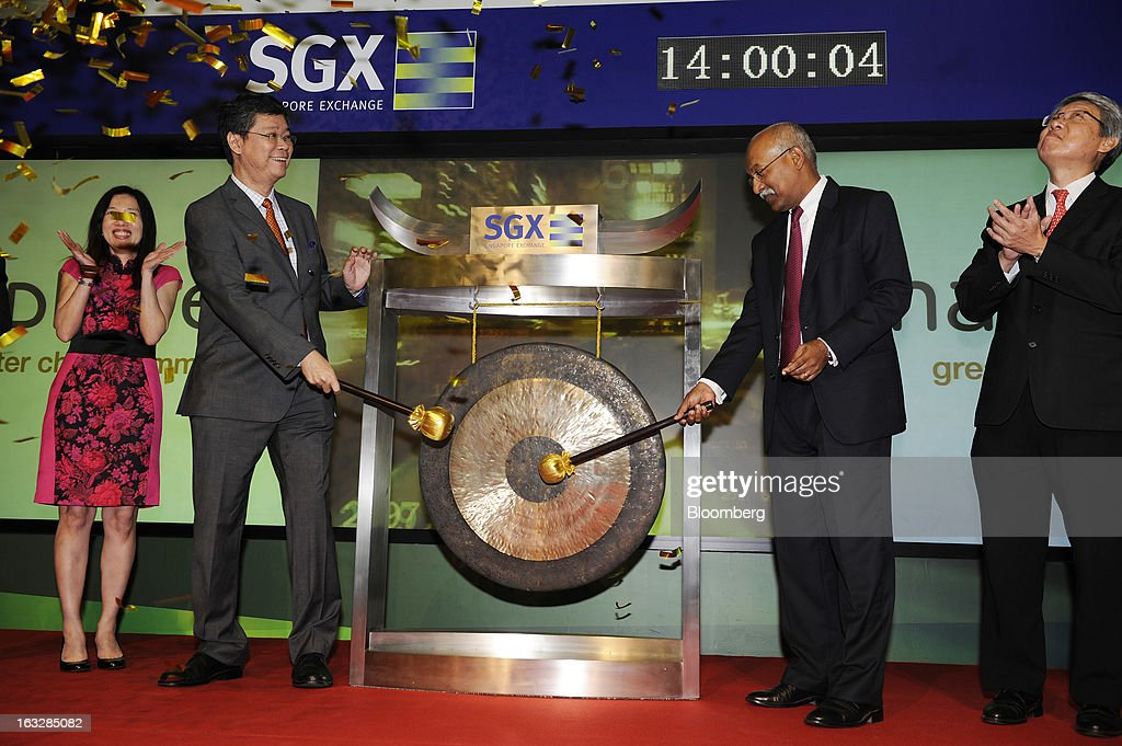 Hiew Yoon Khong, chief executive officer of Mapletree Investments Pte and board director of Mapletree Greater China Commercial Trust, second left, and Muthukrishnan Ramaswami, president of Singapore Exchange Ltd., second right, strike a gong to initiate the trust's listing on the Singapore Exchange during a ceremony at the bourse in Singapore, on Thursday, March 7, 2013. Mapletree Greater China Commercial Trust, Asia's biggest share sale this year, gained on its first trading day as investors were attracted by returns higher than those of comparable properties. Photographer: Munshi Ahmed/Bloomberg via Getty Images
