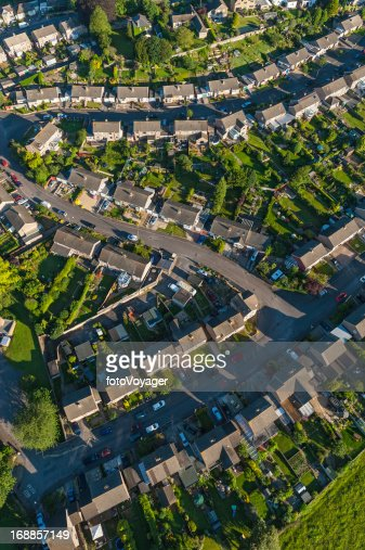 High aerial view over suburban streets homes green gardens