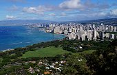 A high altitude view of the southern coast of Oahu, including Waikiki Beach. Mountains can be seen in the distance